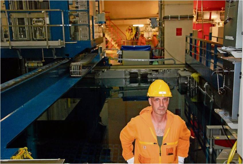 Ingenieur Dominic Ransby plant den Abbau. Im Abklingbecken hinter ihm schimmert die Aufhängevorrichtung im Wasser, an der die Brennelemente hängen. Fotos Fixy