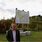 Bürgermeister Andreas Wittenberg vor dem Schild, dass die Bauabschnitte bis 2021 auflistet. Das Areal umfasst unter anderem eine ausgediente Sandkuhle. Foto Gehrke